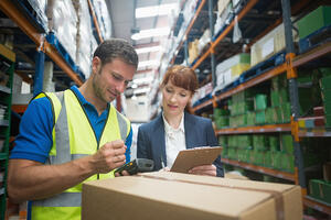 Portrait of manual worker and manager scanning package in the warehouse