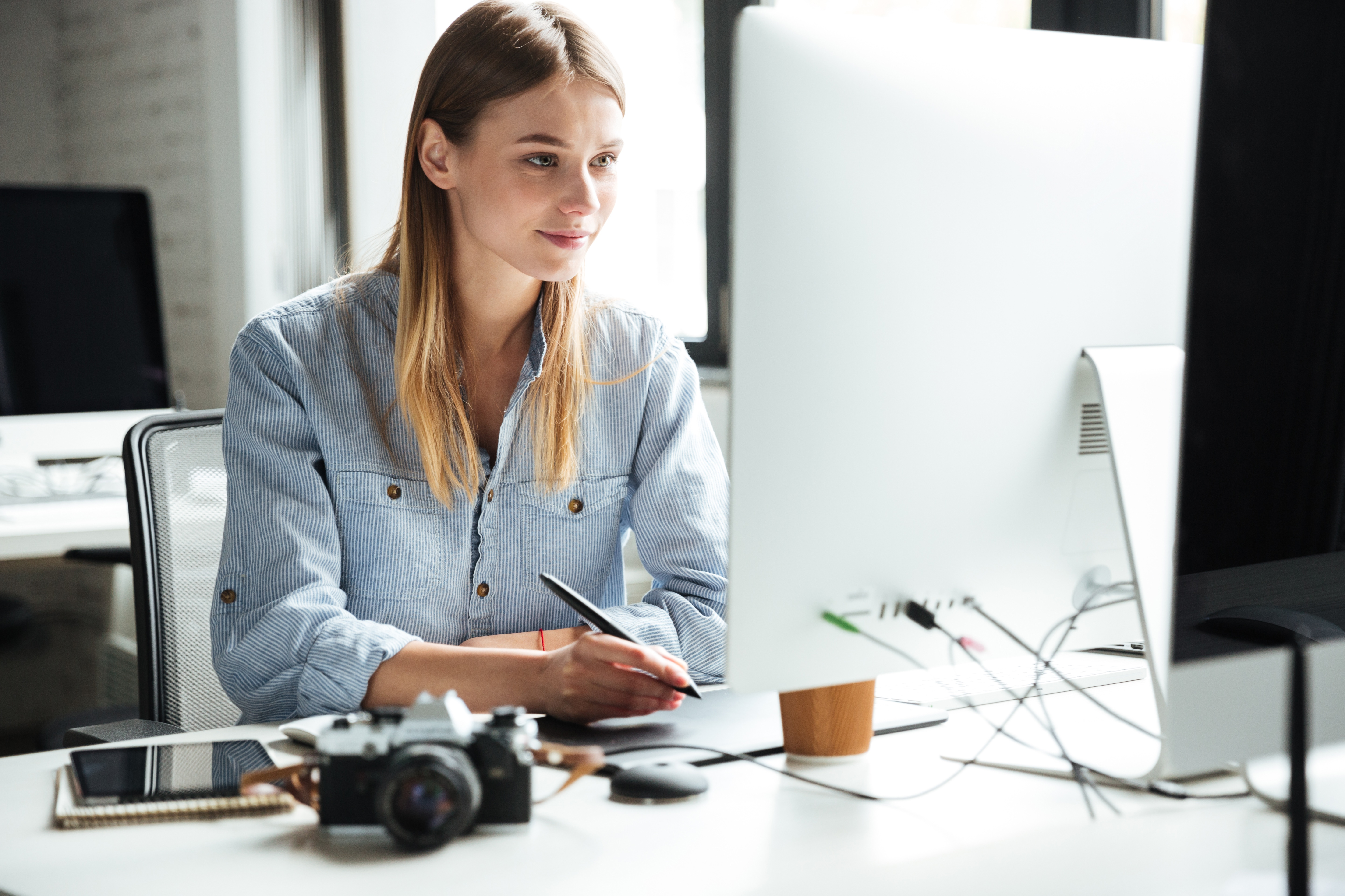 cheerful-young-woman-work-in-office-using-P5R8HHG