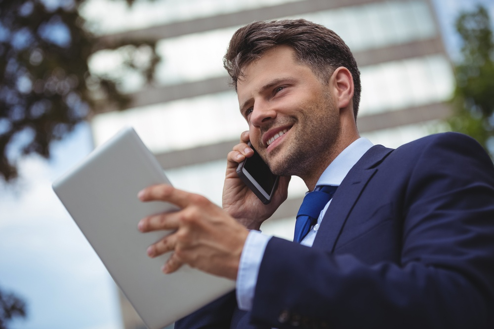 Handsome businessman holding digital tablet and talking on mobile phone